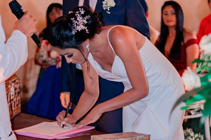 Noiva assinando documento em casamento religioso com efeito civil