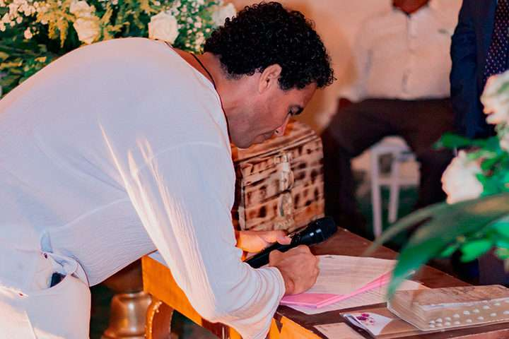 Homem assinando documento de casamento religioso