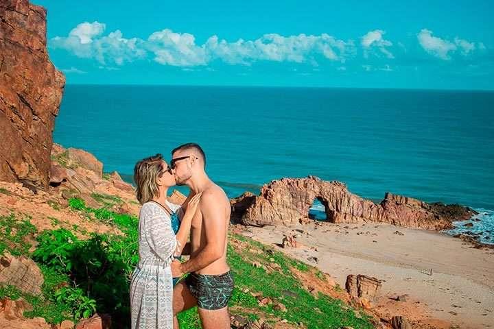 Casal de noivos se beijando na Pedra Furada, em Jericoacoara