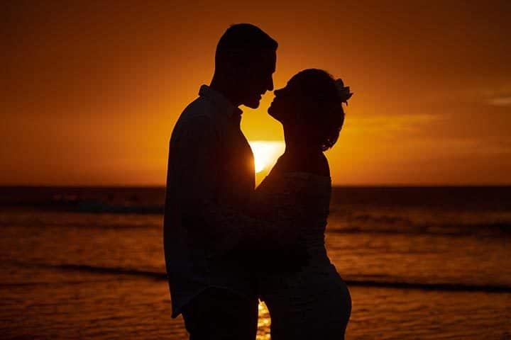 Casal de noivos se beijando no pôr do sol, em pedido de casamento em Jericoacoara
