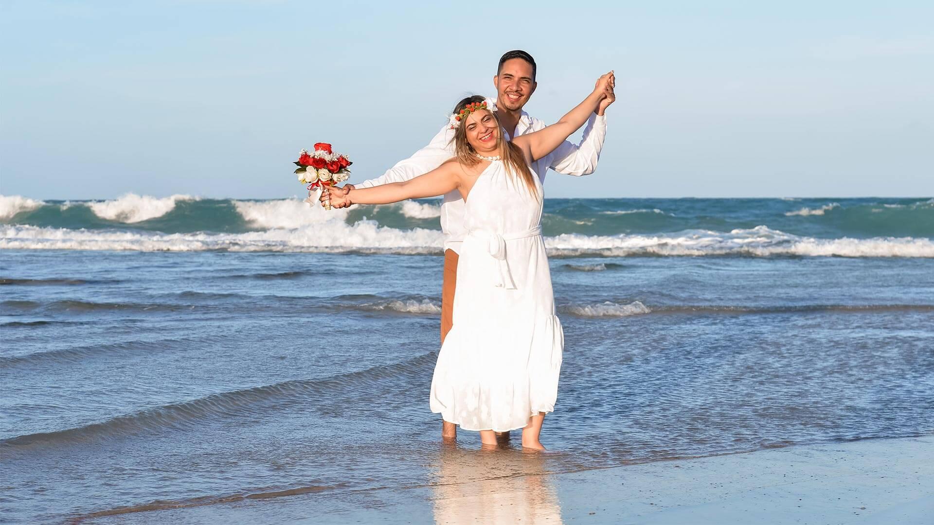 Homem e mulher abraçados, na praia, fazaendo renovação de votos de casamento