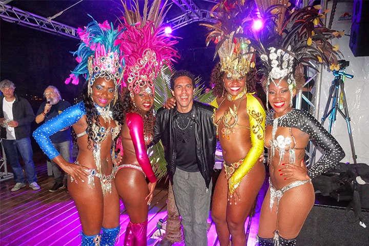 Apresentador Ed Rodrigues abraçando mulatas dançarinas