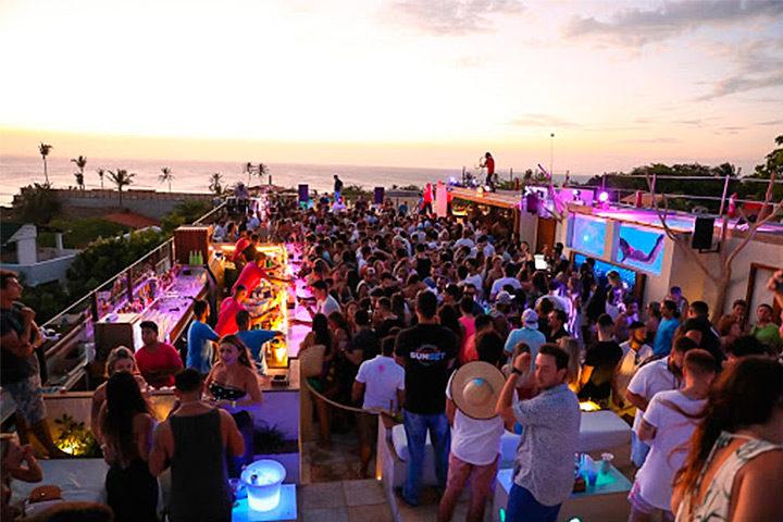 Pessoas dançando em área externa de hotel, no pôr do sol