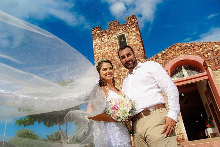 Casal de noivos em frente a igreja de pedra de Jericoacoara no dia de seu casamento
