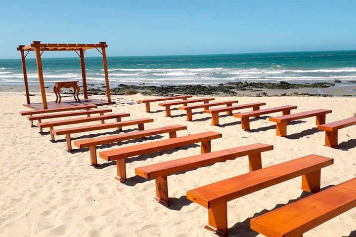 Bancos de madeira e altar de casamento na praia