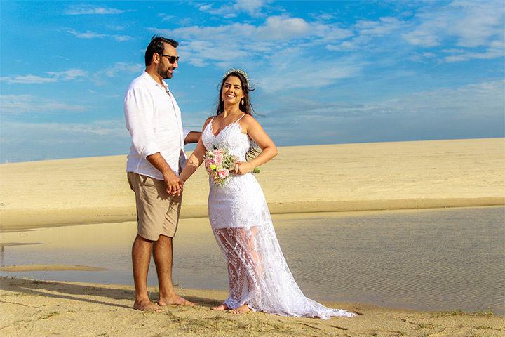 Casal de noivos de mãos dadas na duna de areia de Jericoacoara