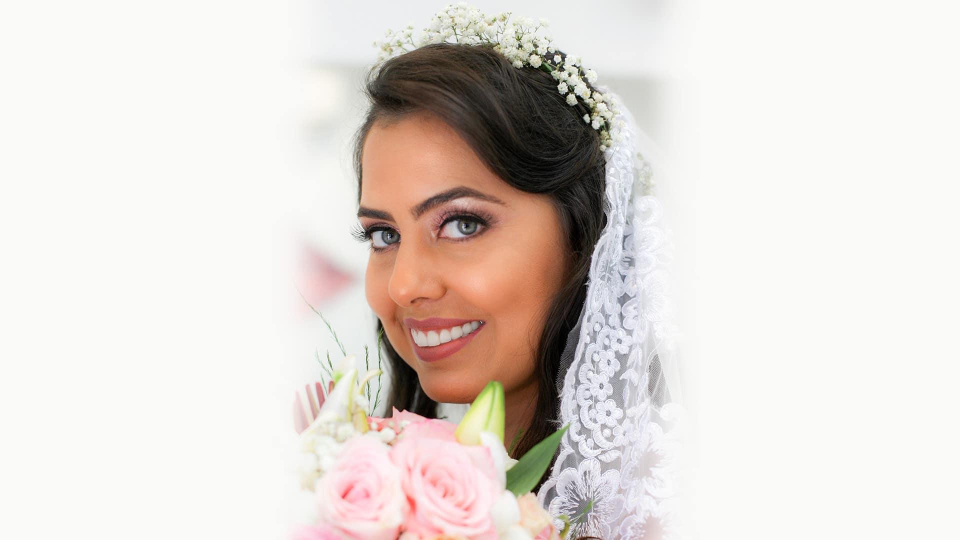 Close de rosto de noiva segurando buquê de flores