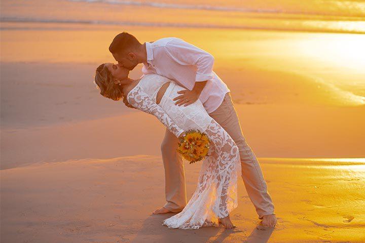 Casal de noivos se beijando na praia, em sessão de fotos após casamento