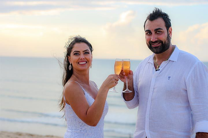 Casal de noivos brindando Elopement na praia