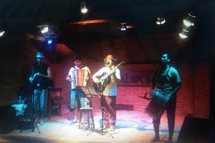 Banda de forró tocando em palco com som e iluminação