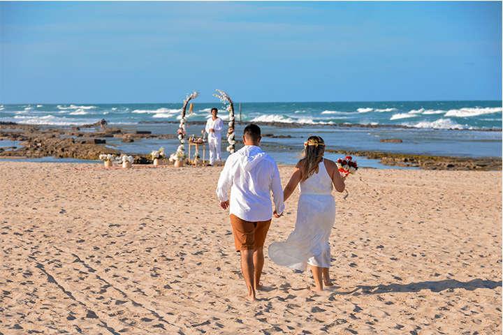 Homem e mulher caminhando na praia em direção ao altar para realizar renovação de Votos