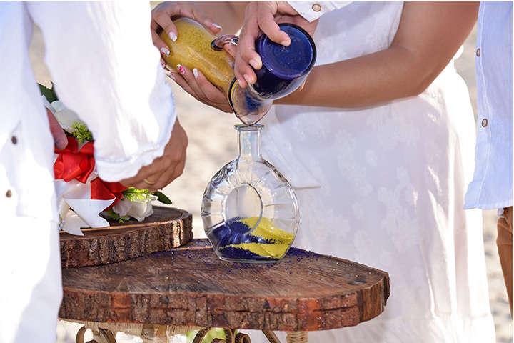Casal despejando areias coloridas em vaso de vidro transparente na Cerimônia das Areias