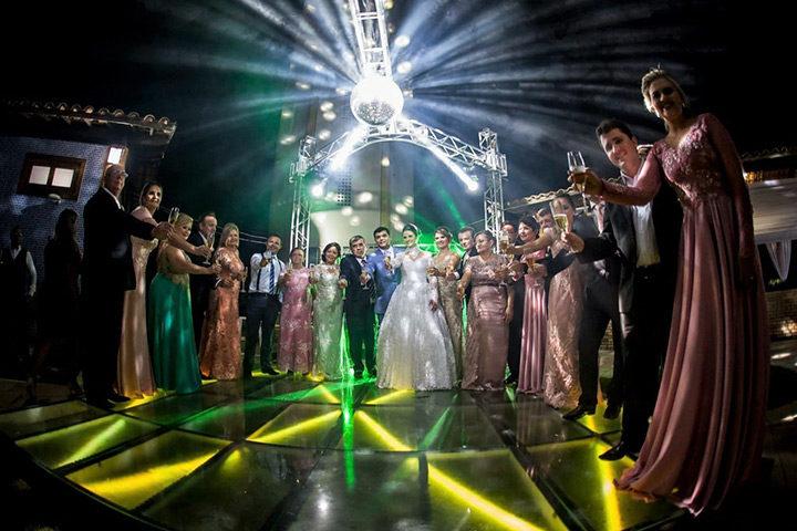 Convidados dançando em tablado de vidro e led colorido