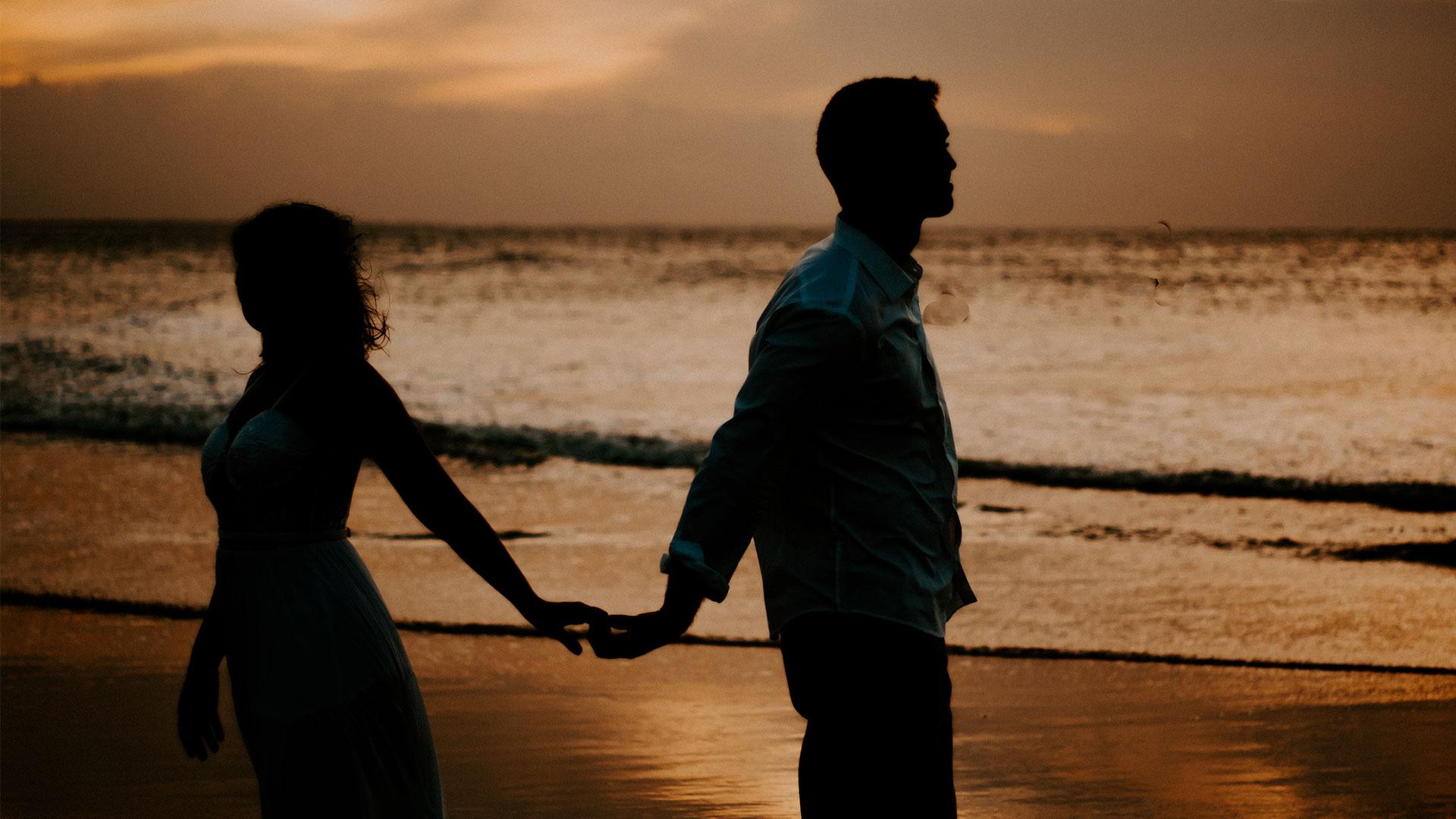 Homem e mulher de mãos dadas, na praia, no pôr do sol