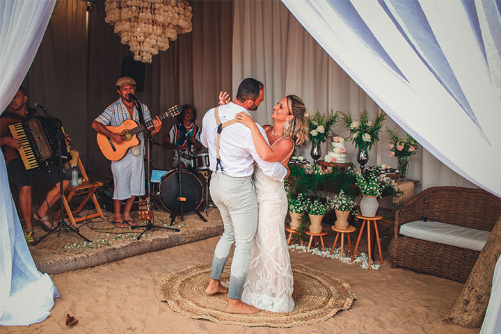 Casal de noivos dançando em restaurante na praia