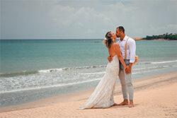 Casal de noivos se beijando na praia