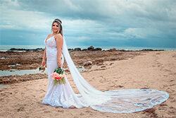 Noiva segurando buquê na praia