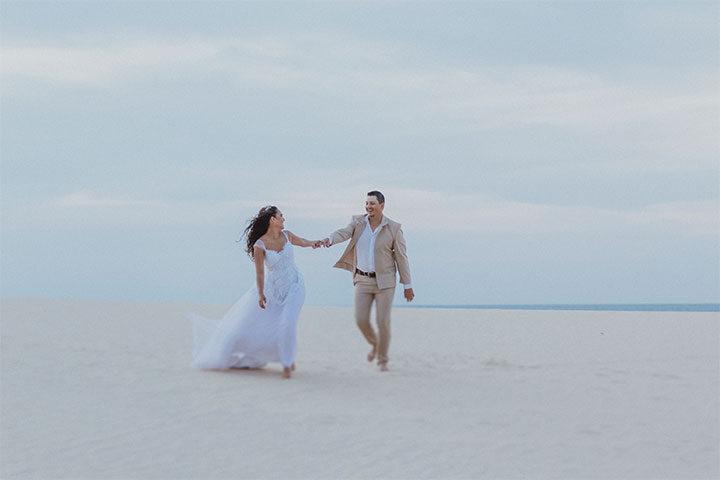 Casal de noivos de mãos dadas caminhando na duna de Jericoacoara