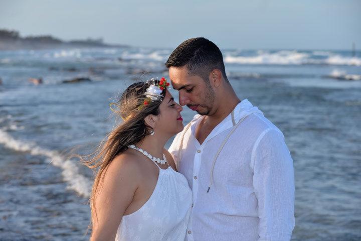 Noiva e noivo abraçados na praia