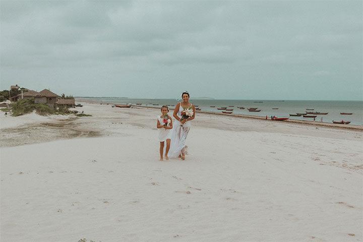 Mãe e filha segurando buquê de flores e caminhando na duna
