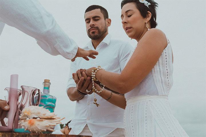 Casal de noivos e celebrante na praia