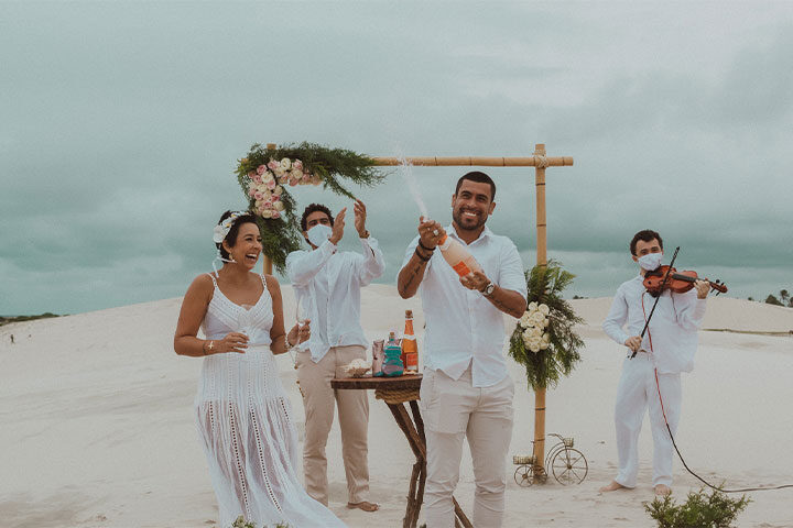 Casal estourando champanhe na praia