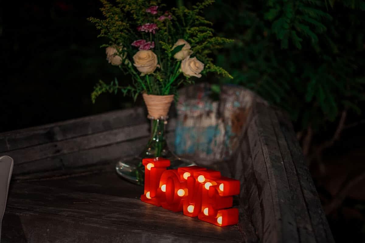 Letreiro luminoso e arranjo de flores em vaso