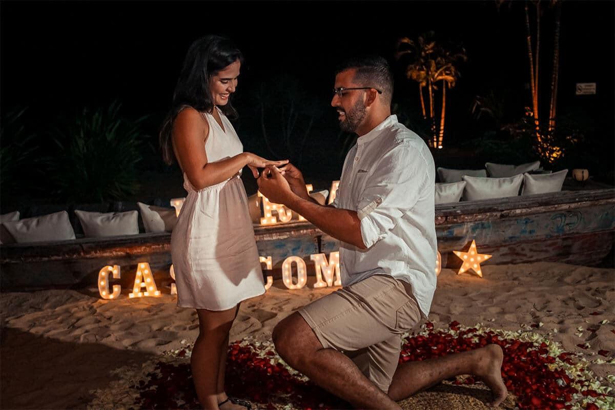 Homem ajoelhado segurando a mão da namorada