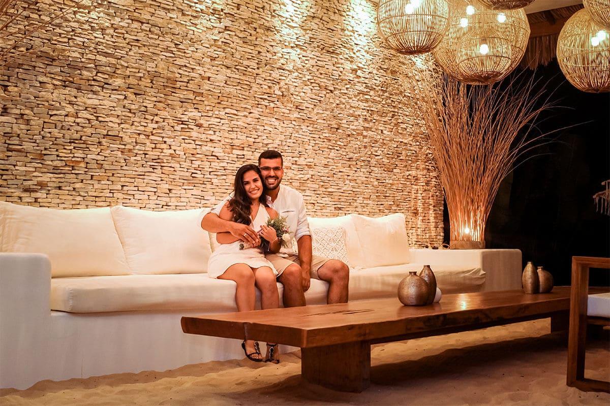 Casal de noivos sentados em sofá de hotel