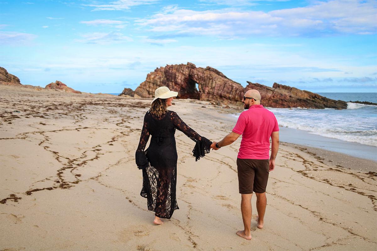 Homem e mulher de mãos dadas na praia