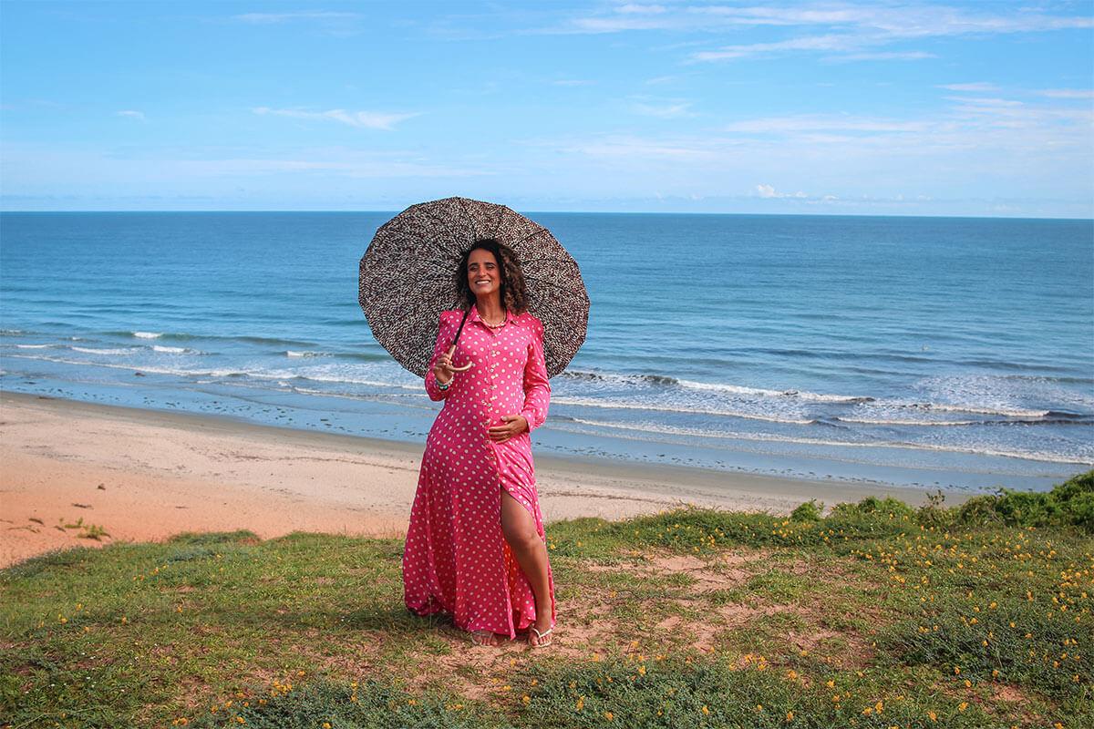 Grávida na praia segurando guarda-chuva