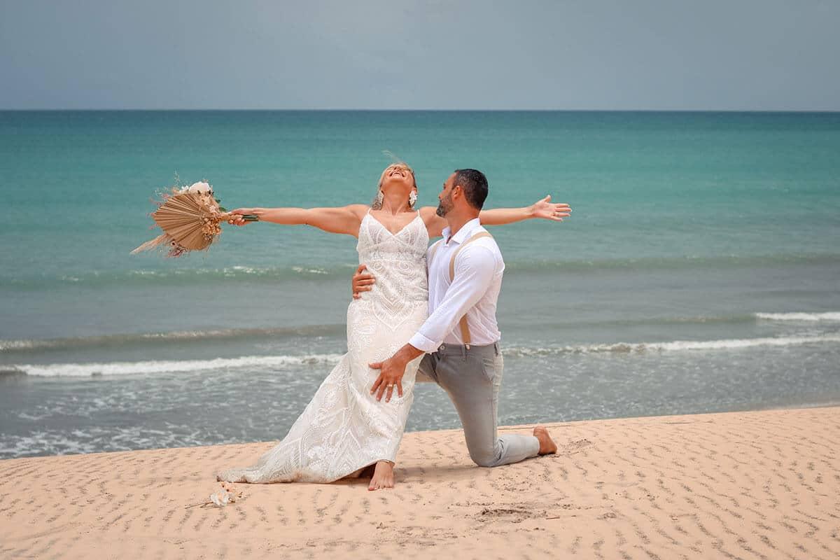 Noiva sentada no colo de noivo na praia