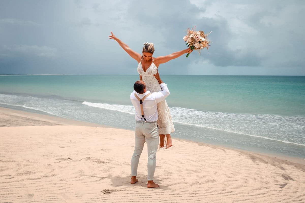 Noivo segurando a noiva em seus braços
