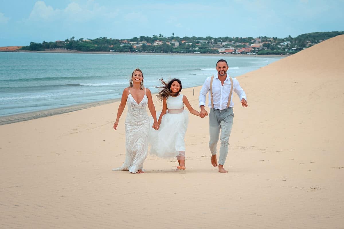 Casal de noivos e filha caminhando na duna de Jeri