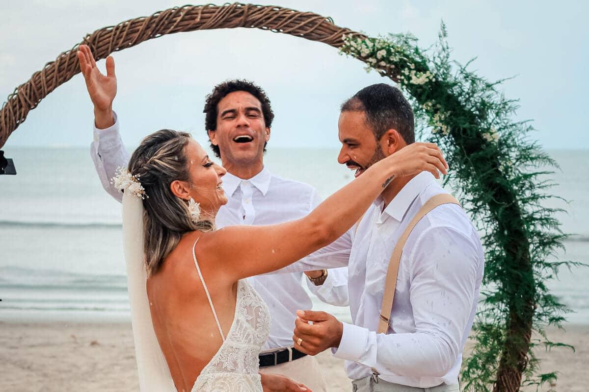 Casal de noivos se abraçando na praia com celebrante