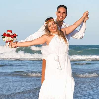 Homem e mulher em pé, na beira da praia comemorando casamento