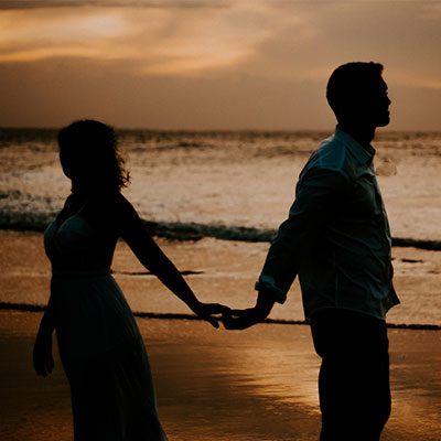Casal de noivos de mãos dadas na praia