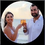 Casal de noivos brindando com taça de champanhe na praia