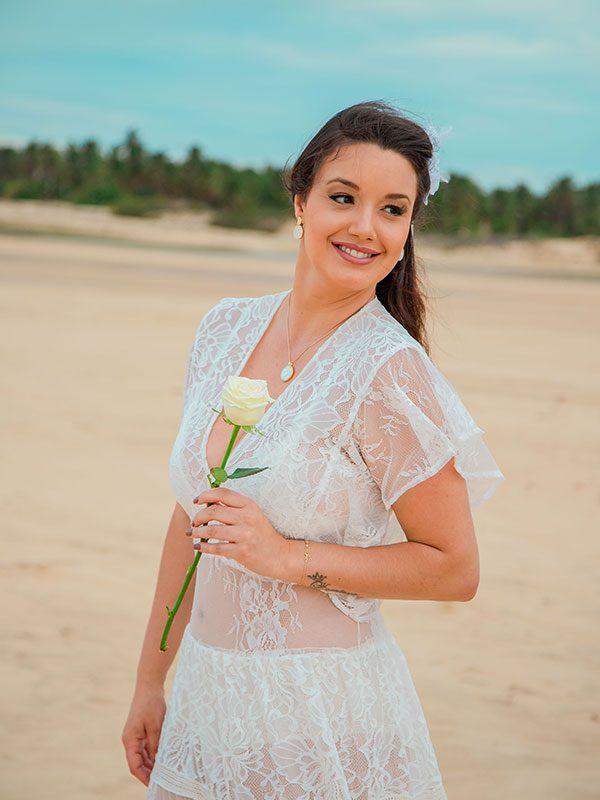 Noiva segurando botão de rosa na duna de Jericoacoara