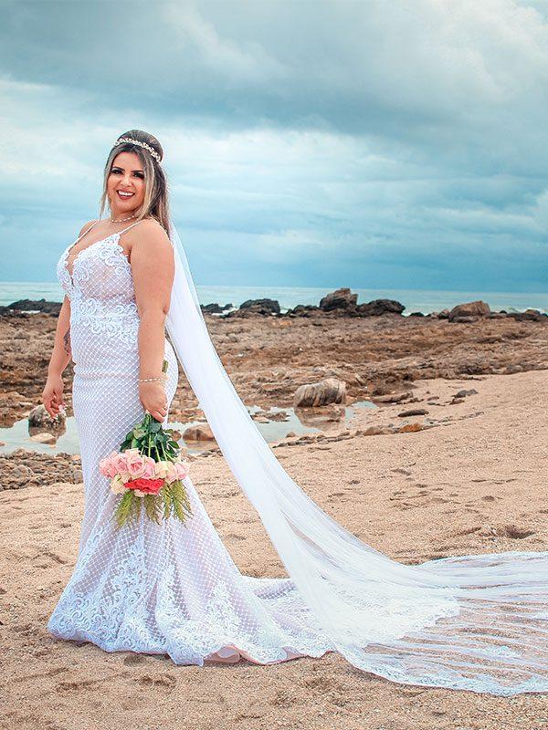 Noiva segurando buquê de flores na praia