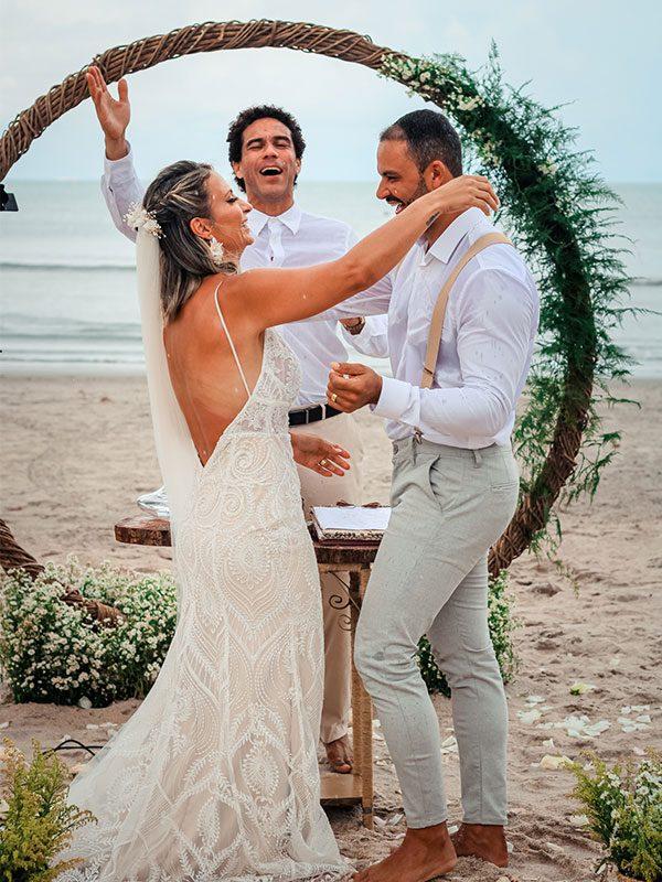 Casal de noivos com celebrante na praia