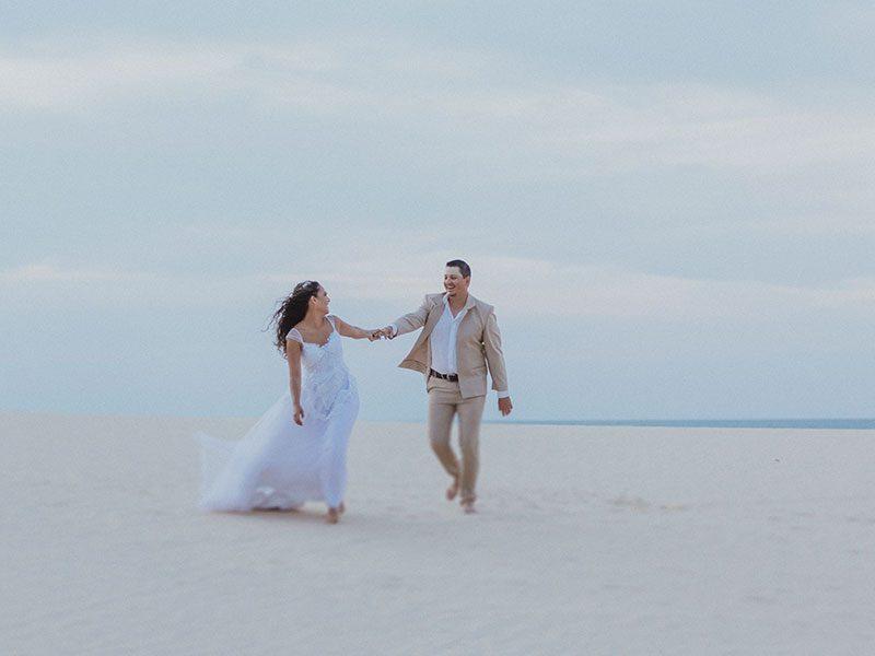 Casal de noivos caminhando na duna de Jericoacoara