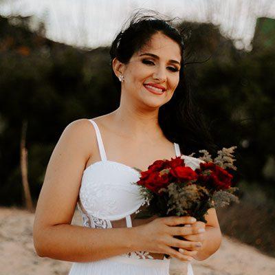 Noiva sorrindo e segurando buquê