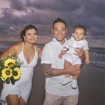 Noiva e noivo segurando filho no colo na praia