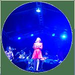 Cantora realizando show em palco com iluminação