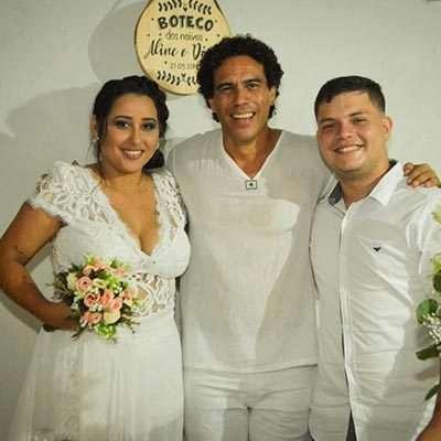 Noiva segurando buquê de flores, abraçada com celebrante do casamento e o noivo