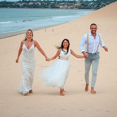 Casal de noivos caminhando com filha, de mãos dadas na duna do pôr do sol